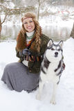 Happy young woman standing with siberian husky dog. In winter forest Stock Photography