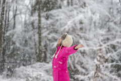 Happy young woman standing in snow blizzard with her arms spread Stock Photo