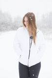 Happy young woman standing in the snow. Young woman outdoors hiking during a winter snow storm Stock Photos