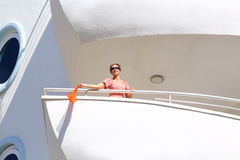 Happy young woman stands on balcony Stock Images