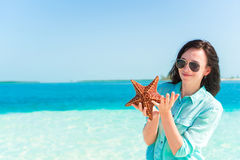 Happy young woman with starfish on white beach in in the nature reserve Royalty Free Stock Images