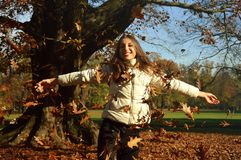 Happy young woman staying under tree when leaves are falling in Autumn Stock Photography