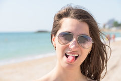 Happy Young Woman Sticking Out Tongue On Beach Royalty Free Stock Photos