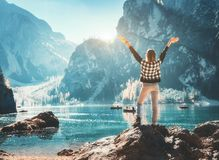 Happy young woman on the stone with raised up arms stock images