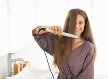Happy young woman straightening hair in bathroom Royalty Free Stock Images