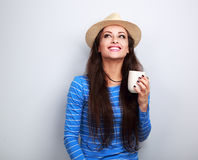 Happy young woman in straw hat drinking coffee with thinking fac Stock Images
