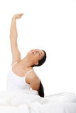 Happy young woman stretching in bed Stock Image