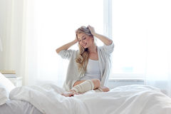 Happy young woman stretching in bed at home Stock Images