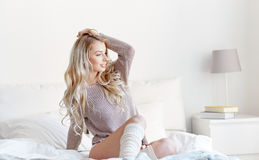 Happy young woman stretching in bed at home Stock Photography