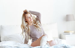 Happy young woman stretching in bed at home Royalty Free Stock Image