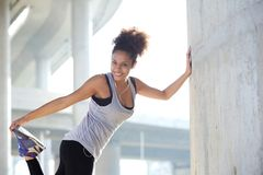 Happy young woman stretching leg muscles outdoors Royalty Free Stock Photography