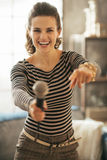 Happy young woman stretching microphone in camera Stock Images