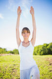 Happy young woman stretching outside. In a sunny meadow Stock Photography