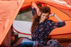 Happy young woman stretching relax at tent. Young woman just wake up after sleeping in touristic tent stock image