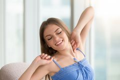 Beautiful young woman stretching arms, feeling fresh happy, head. Happy young woman stretching while relaxing at home, head shot portrait of smiling rested girl Royalty Free Stock Photos