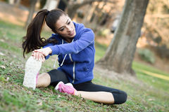Happy young woman stretching before running outdoors Royalty Free Stock Photo