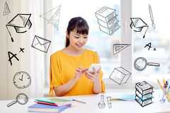 Happy young woman student with smartphone at home. People, education, high school, technology and learning concept - happy asian young woman student with Stock Image
