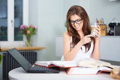 Happy young woman studying in kitchen Royalty Free Stock Photo