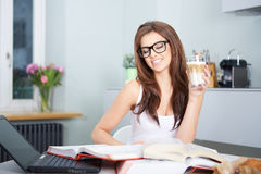 Happy young woman studying in kitchen Stock Image