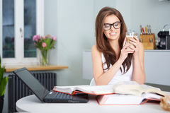 Happy young woman studying in kitchen Stock Images