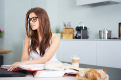 Happy young woman studying in kitchen Royalty Free Stock Image