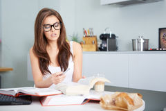 Happy young woman studying in kitchen Stock Photos