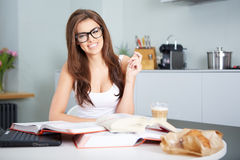 Happy young woman studying in kitchen Royalty Free Stock Images