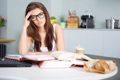 Happy young woman studying in kitchen Royalty Free Stock Photos