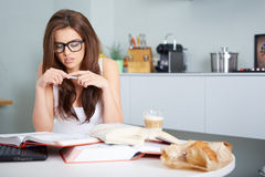 Happy young woman studying in kitchen Royalty Free Stock Photography