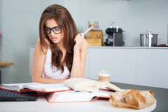 Happy young woman studying in kitchen Stock Photography