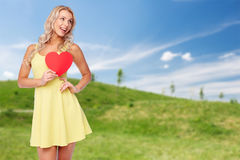Happy young woman in summer dress with red heart Stock Photography
