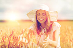 Happy young woman in sun hat on cereal field. Nature, summer holidays, vacation and people concept - happy young woman in white dress and sun hat enjoying sun on Royalty Free Stock Image