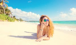 Happy young woman with sunglasses laying on beach. Royalty Free Stock Images