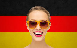 Happy young woman in sunglasses over german flag Stock Photography