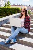 Happy young woman in sunglasses sitting on the city stairs and using laptop Stock Photography