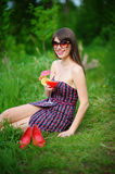 Happy young woman in sunglasses sitting on the grass with a cock Stock Photography
