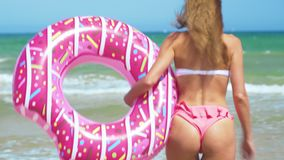 Happy young woman, with sunglasses and swim toy, pink donut, to run water on beach. Playful woman having fun on the. Beach stock video footage