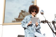 Happy young woman in sunglasses using tablet computer. While sitting on a motorbike outdoors Royalty Free Stock Image