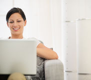 Happy young woman surfing net on laptop Stock Image