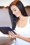 Happy young woman surfing on a tablet-pc Royalty Free Stock Photo