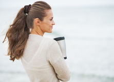 Happy young woman in sweater on beach with cup of hot beverage Royalty Free Stock Photos