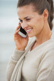 Happy young woman in sweater on beach talking cell phone Stock Image