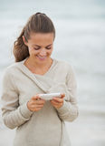 Happy young woman in sweater on beach writing sms Stock Images