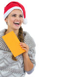 Happy young woman in sweater and christmas hat with letter Stock Images