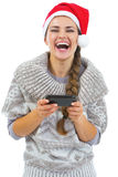 Happy young woman in sweater and christmas hat reading sms Royalty Free Stock Images