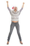 Happy young woman in sweater and christmas hat rejoicing Stock Photos