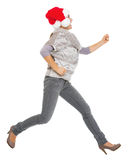Happy young woman in sweater and christmas hat running sideways Stock Images