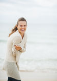 Happy young woman in sweater on coldly beach. Happy young woman with long hair in sweater on coldly beach royalty free stock photo