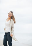 Happy young woman in sweater having fun time on lonely beach Stock Photography