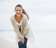 Happy young woman in sweater having fun time on lonely beach Stock Images